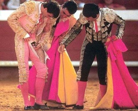 Drei Stierkämpfer untersuchen das Glied eines der Kämpfer.