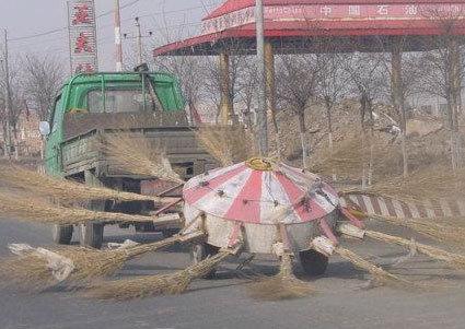 Ein Straßenreinigungsfahrzeug mit einem gigantischen Besen.