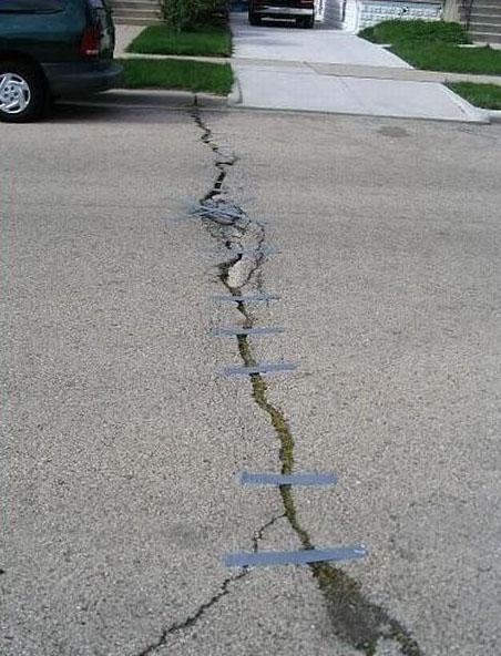 In einer Straße ist ein großer Riss. Dieser wurde mit Klebeband geklebt.