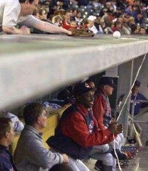 Ein Baseballspieler hat einen Ball an einer Leine, den ein Zuschauer nehmen möchte.