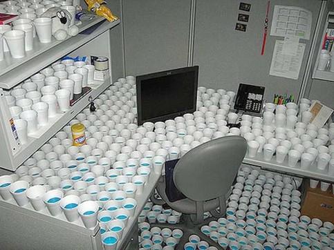In einem Büro wurde ein Arbeitsplatz komplett mit gefüllten Pappbechern zugestellt.