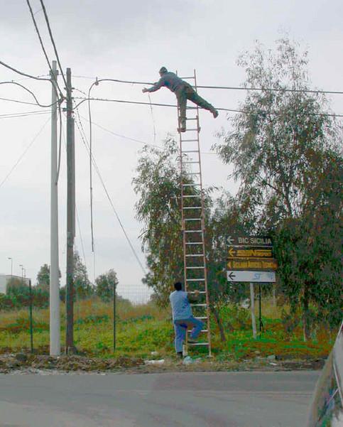 Eine Leiter wird an eine Stromleitung gelehnt und benutzt.