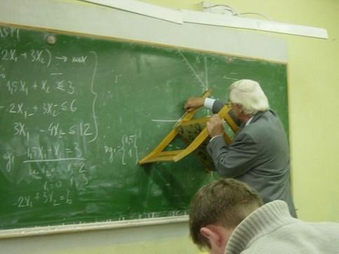 Ein Mathe-Lehrer mal mit einem Stuhl auf einer Tafel.