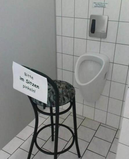 """Ein Stuhl steht vor einem Pissoir. An diesem hängt ein Zettel: """"Bitte im Sitzen pinkeln!"""""""