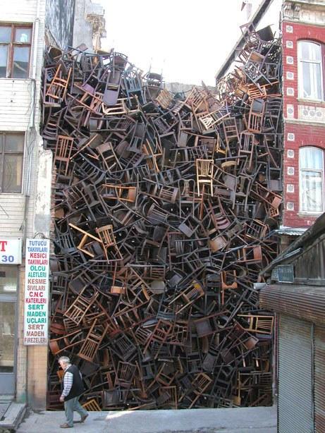 Ein riesiger Haufen Stühle aus Holz wird zwischen zwei Häusern gelagert.