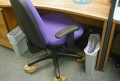 Ein Stuhl steht auf Ziegelsteinen statt auf Rollen.