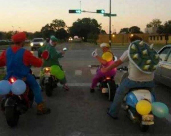 Vier Männer sind als Super Mario, Luigi und zwei anderen Nintendo-Figuren verkleidet und fahren stehen auf Rollern an einer Ampel.