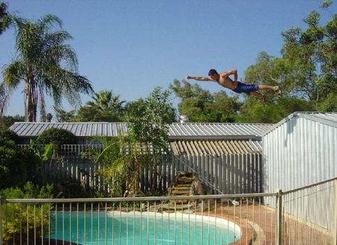 Ein Mann fliegt in Superman-Pose von einem Dach in einen Pool.