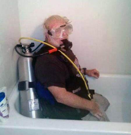 Ein Mann kniet mit kompletter Tauchausrüstung inklusive Druckluftflasche in einer Badewanne. Wahrscheinlich will er gleich in der Badewanne tauchen.
