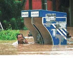 Ein Mann steht im Hochwasser an einer überfluteten Telefonzelle und versucht zu telefonieren.