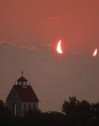 Hinter einer Kirche geht der Mond auf, und er sieht wie zwei Teufelshörner aus.