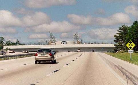 Ein Auto fährt auf eine Brücke zu, die sehr niedrig wirkt.