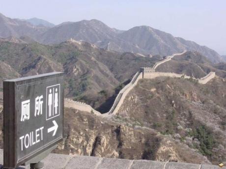 Ein Schild zu Toiletten zeigt die chinesische Mauer entlang.