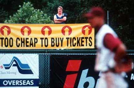 """Ein Mann steht bei einem Baseballspiel als Zaungast hinter einem Zaun. Am Zaun hängt ein Transparent """"TOO CHEAP TO BUY TICKETS"""""""