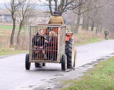 Ein Traktor hat einen Käfig geladen, in dem zwei Frauen mit Kopftüchern sitzen.