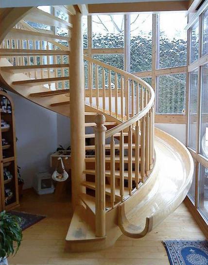 An der Außenseite einer Holztreppe ist eine Rutsche installiert.
