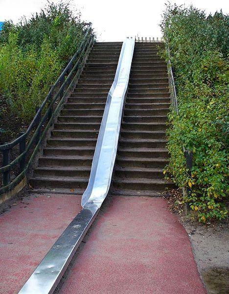 An einer langen Treppe ist eine Rutsche installiert. So kann man bequem die Treppe herunterrutschen anstatt zu laufen.