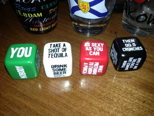 """Vier Würfel, die bei einem Trinkspiel vorgeben, was getan werden muss. Zum Beispiel: """"You take a shot of Tequila as sexy as you can the do 5 crunches""""."""