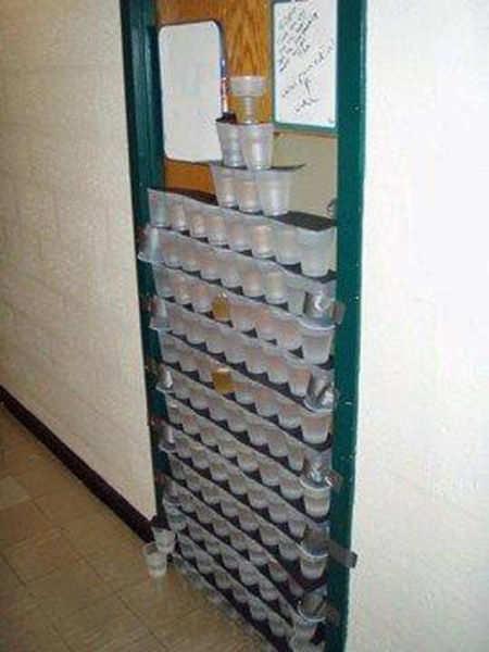 Eine Tür wurde mit gefüllten Getränke-Bechern zugestellt. Wer durch die Tür will, muss alle Becher einzeln herunter nehmen.