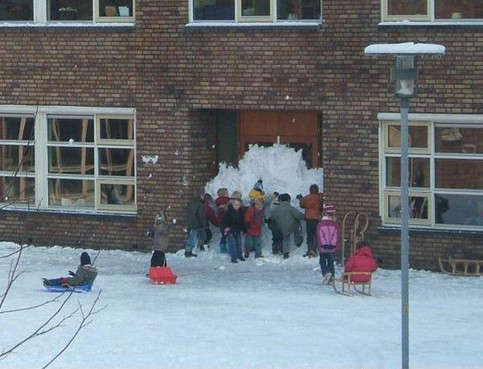 Schüler verbauen den Eingang einer Schule mit Schnee.