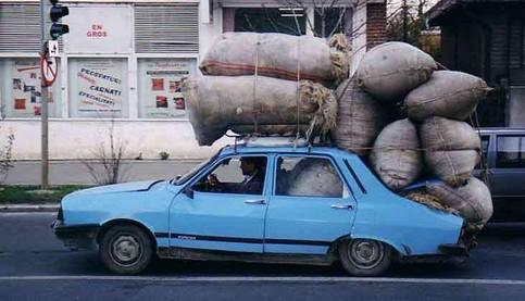 Ein Auto transportiert einen Haufen dicker Säcke, die auf dem Auto festgeschnallt sind.
