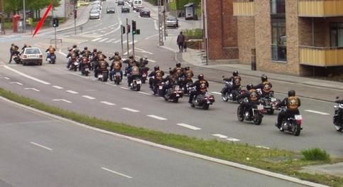 Eine Motorrad-Gang macht einen Ausflug. Ein Auto fährt ein Motorrad an, das vorfährt.
