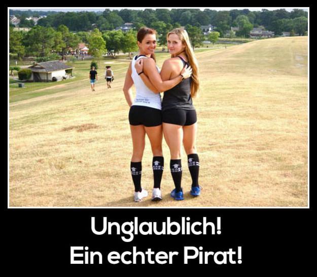 Zwei junge Frauen schauen über ihre Schultern in die Kamera. Im Hintergrund ist ein Mann als Pirar verkleidet.