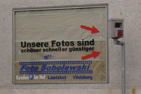 """Ein Werbeplakat neben einem Blitzer: """"Unsere Fotos sind schöner, schneller, günstiger."""""""