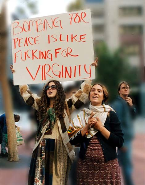 "Eine Frau hält ein Plakat in die Höhe: ""Bombing for Peace is like fucking for Virginity""."