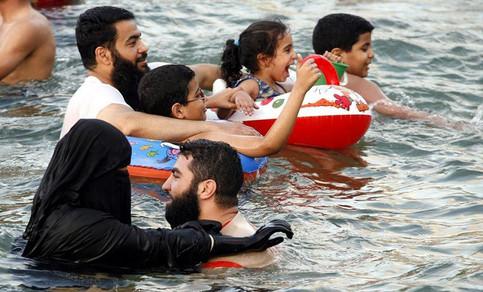 Eine verhüllte Muslima badet im Meer.