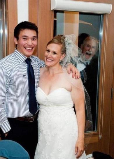 Eine Frau im Hochzeitskleid posiert mit einem Mann. Im Hintergrund lacht ein Mann verrückt durch eine Glasscheibe.