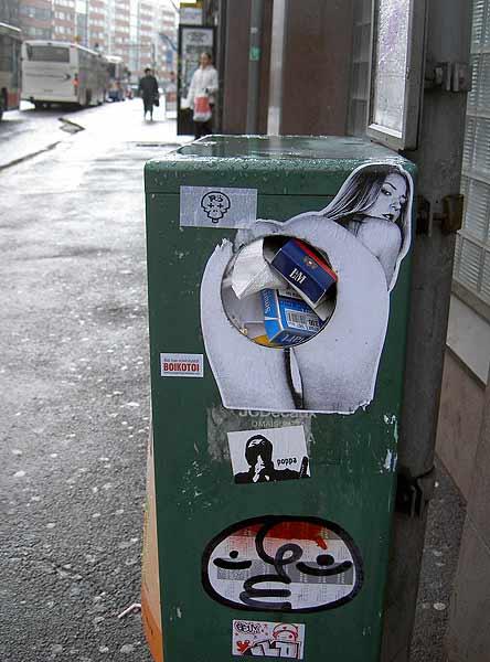 Ein Aufkleber auf einer Mülltonne, der eine Frau von hinten zeigt. Der Müll kann also in die Frau geschoben werden.