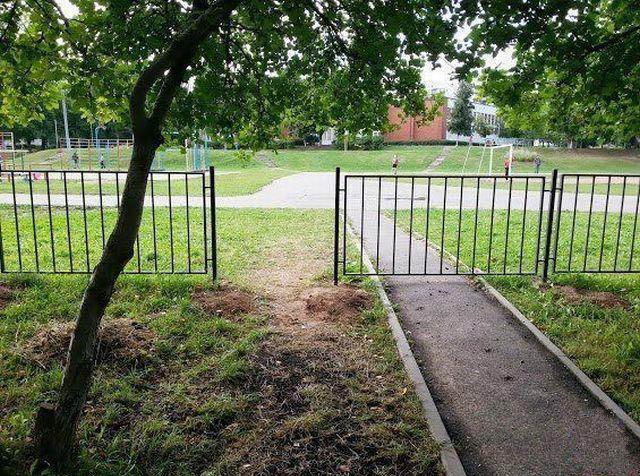 Ein Zaun wurde so installiert, dass ein kreuzender Weg versperrt wurde, während sich neben dem Weg eine Öffnung im Zaun befindet.