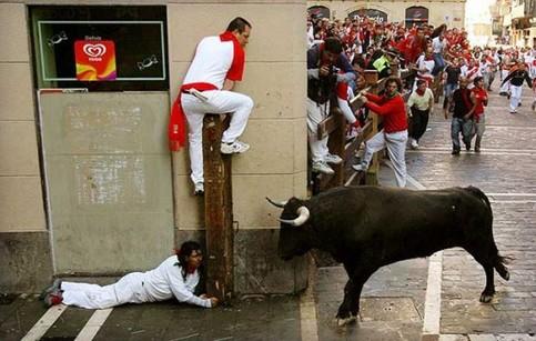 Männer verstecken sich in einer Straße vor einem Stier, den sie vorher durch die Straße getrieben haben.