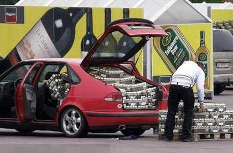 Ein Mann lädt palettenweise Bier in ein Auto.