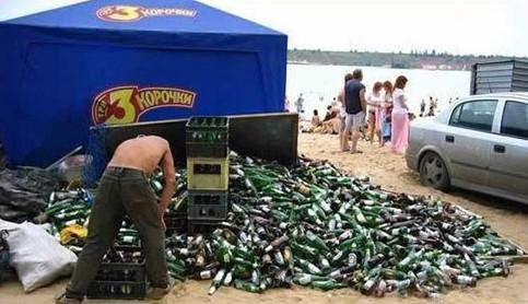 An einem Strand liegt ein riesiger Haufen leerer Bierflaschen.