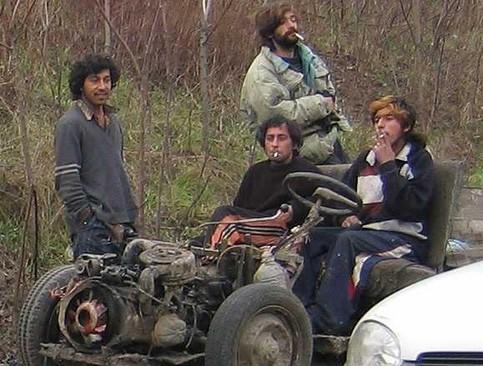 Drei Männer sitzen lässig rauchend auf einem Haufen Schrott, der mal ein Auto war.