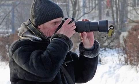 Ein Mann schaut durch einen Fotoapparat, auf das Objektiv hat sich ein Vogel gesetzt.