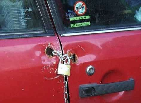 Eine Autotür ist mit einer Kette und einem Vorhängeschloss abgeschlossen.