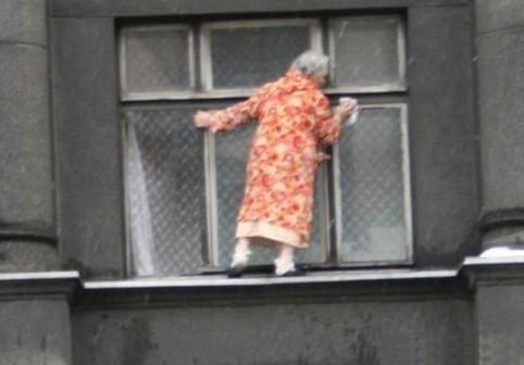 Eine Oma ist aus dem Fenster auf die Fensterbank gekletter, um die Fenster zu putzen.