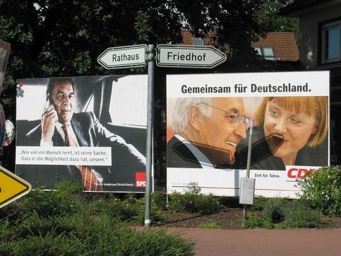 Ein Wegweiser vor zwei Bundestagswahl-Plakaten von Schröder, Stoiber und Merkel. Einer zeigt zum Rathaus, der andere zum Friedhof.