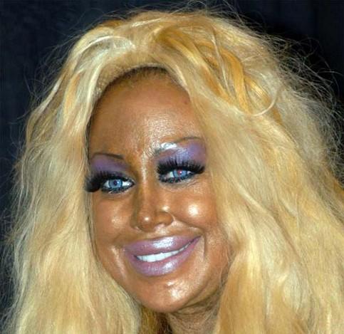 Eine Frau mit schrecklicker Schminke, verbrannter Haut und einer Perücke.