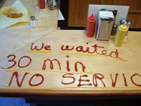 """Auf dem Tisch in einem Restaurant ist mit Ketchup und Senf geschrieben """"We waited 30 Min. No Service!"""""""