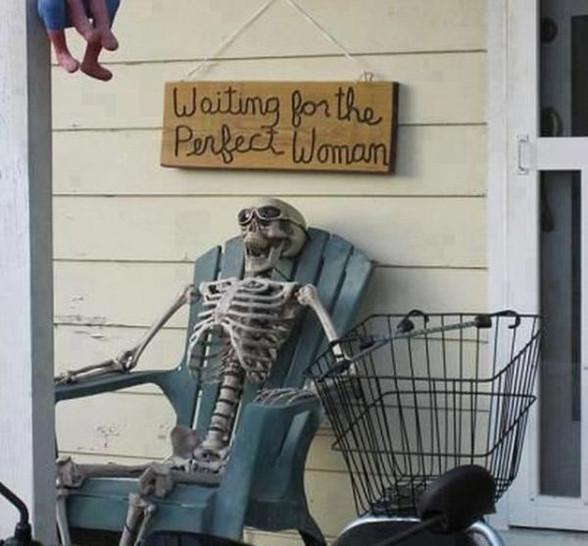 """Ein Skelett sitzt auf einem Stuhl. Über ihm hängt ein Schild """"Waiting for the perfect woman"""","""