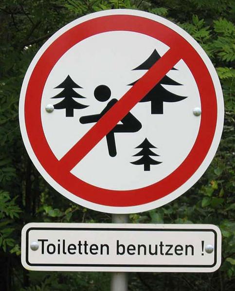 Ein Schild gebietet, im Wald bitte die Toiletten zu benutzen.