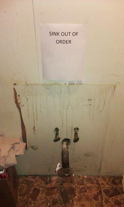 """An einem Platz, wo früher mal ein Waschbecken hing, hängt ein Schild: """"Sink out of order""""."""