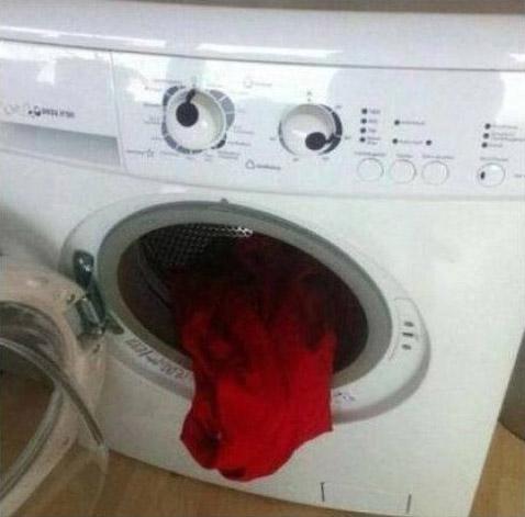 Aus einer Waschmaschine hängt ein rotes Handtuch so heraus, dass die Waschmaschine mit den beiden Drehknöpfen als Augen und dem Handtuch als Zunge sehr menschlich aussieht.