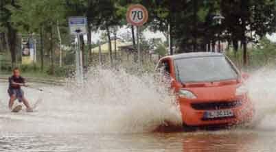 Ein Mann wird auf Wasserski auf einer überschwemmten Straße von einem Auto gezogen.