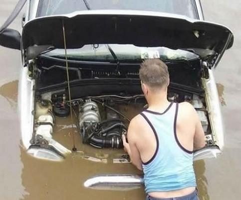 Ein Mann versucht einen Motor zu reparieren, der tief unter Wasser steht.