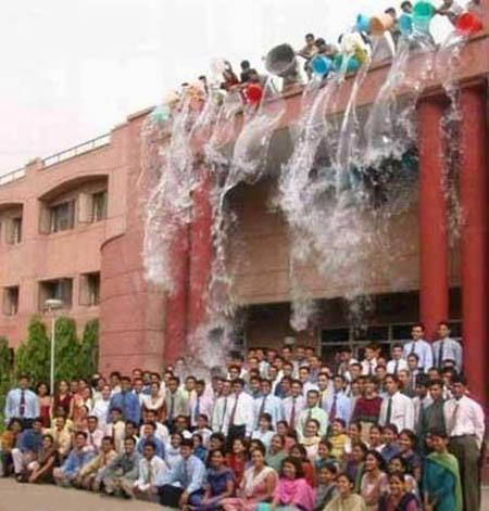 Männer kippen viele Eimer Wasser auf darunter stehende Absolventen.